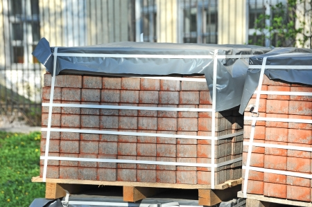 brick earth: Stack of orange clay brick on pallet Stock Photo
