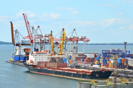 loading cargo: Container stack and ship under crane bridge Editorial