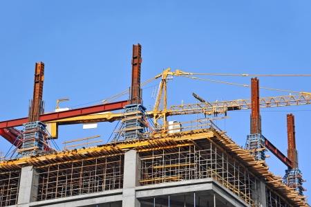 Beton bekisting en kraan op bouwplaats Redactioneel