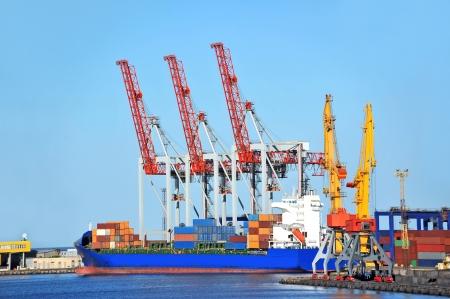 Container stack and ship under crane bridge Editorial
