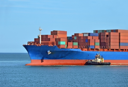 Tugboat assisting container cargo ship to harbor quayside photo