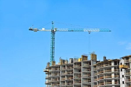 Crane and building construction site against blue sky Stock Photo - 21119698