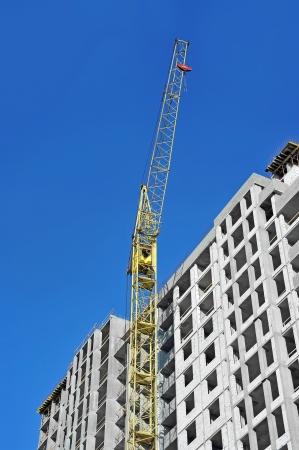 Crane and building construction site against blue sky Stock Photo - 21119700