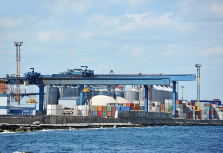 Port cargo crane and container over blue sky background photo