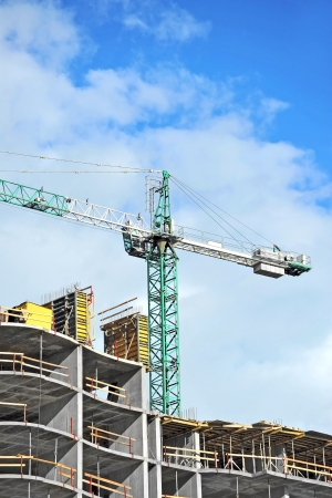 Crane and building construction site against blue sky Stock Photo - 21632531
