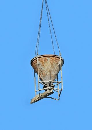 Crane lifting concrete mixer container against blue sky photo