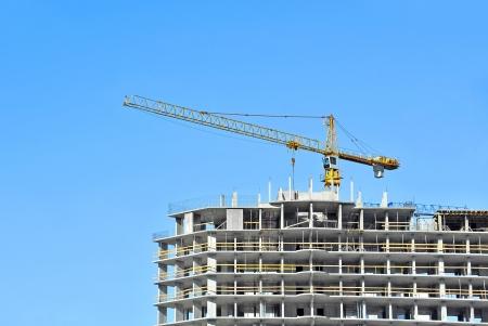Crane and building construction site against blue sky Stock Photo - 21632293