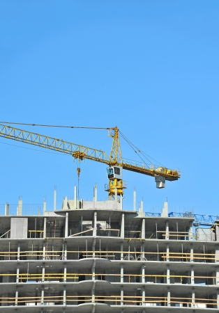Crane and building construction site against blue sky Stock Photo - 21632276