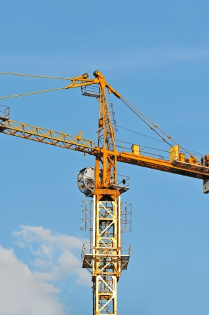Yellow construction tower crane against blue sky photo
