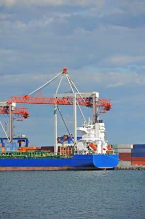 Container stack and cargo ship under crane bridge photo