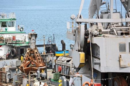 crane bucket: Rusty scoop of cargo crane on the ship deck