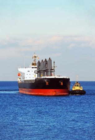 Sleepboot helpen bulkcarrier naar de haven kade Stockfoto