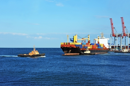 tugboat: Tugboat assisting container cargo ship to harbor quayside