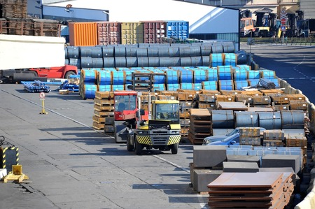 Stacked steel metal sheet and roll, ready for shipment in port photo