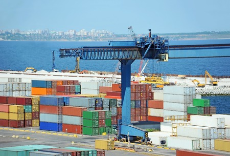 Port cargo crane and container over blue sea background photo