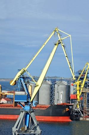 Bulk cargo ship under port crane bridge, Odessa, Ukraine photo