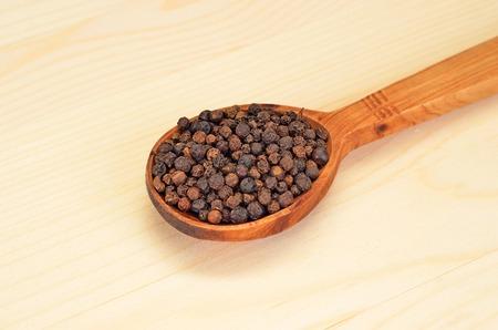 flavorings: Black pepper granules in wooden spoon on natural background