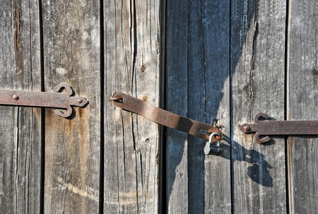 Rusty lock on old vintage rural wooden gate photo