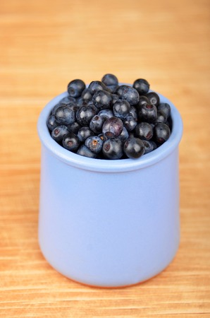 Blueberry in cup on vintage wooden background photo