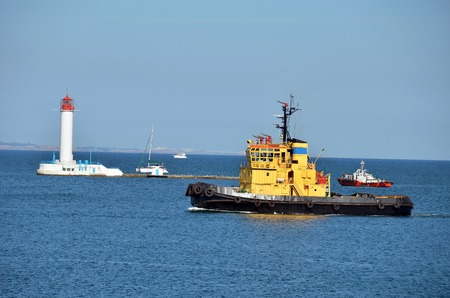 tugboat: Tugboat in harbor quayside, over lighthouse in Odessa, Ukraine