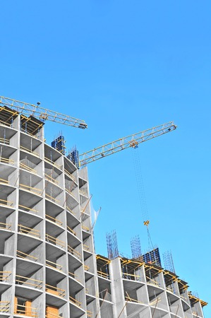 concrete structure: Crane and building construction site against blue sky