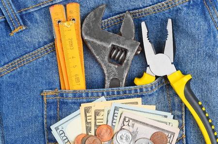 ganancias: Concepto de Ganancias - dinero y herramienta en bolsillo de los tejanos