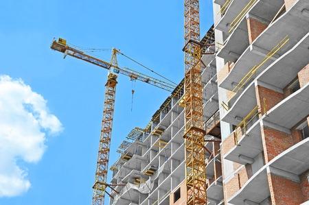 青い空を背景にクレーンとビルの建設現場