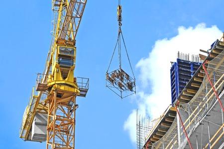 Kraan en de bouw bouwplaats tegen de blauwe hemel