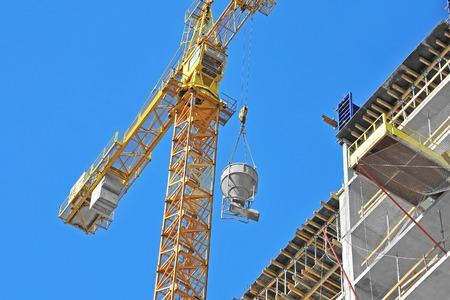 concrete: Crane lifting concrete mixer container against blue sky