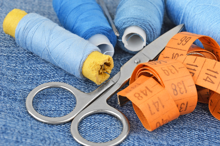 backround: Sewing kit from threads, scissors and meter on jeans backround Stock Photo