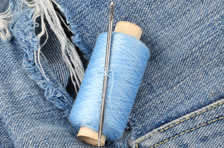 backround: Threads and needle on jeans backround, wear repair concept