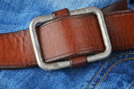 uomo rosso: Blue jeans with natural leather belt, close up