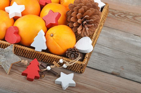 christmas decor: Orange in wickered tray on wooden background with Christmas decor Stock Photo