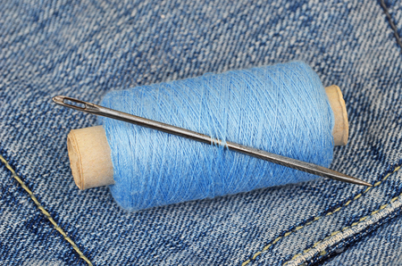 backround: Threads and needle on blue jeans backround