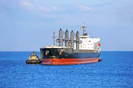 tugboat: Tugboat assisting bulk cargo ship to harbor quayside Stock Photo