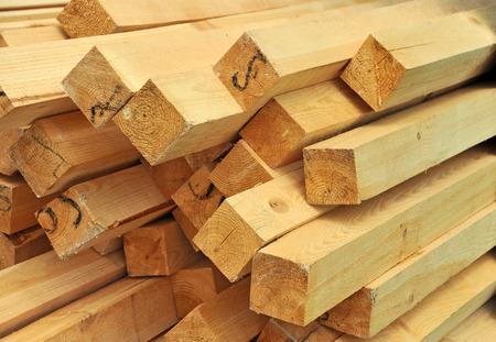 materiales de construccion: viga de madera fresca, apilados en el sitio de construcción Foto de archivo