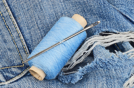 crafty: Threads and needle on jeans backround, wear repair concept