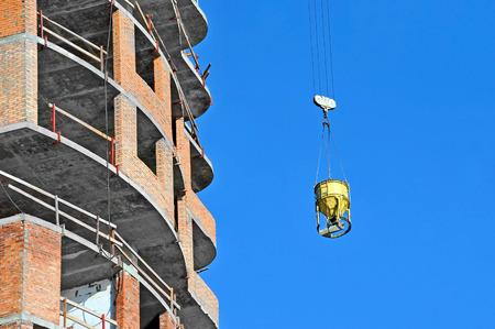 windlass: Mobile crane lifting concrete mixer container against blue sky