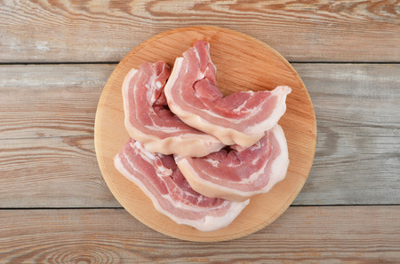 uncooked bacon: Raw bacon steaks on board with wooden background Stock Photo