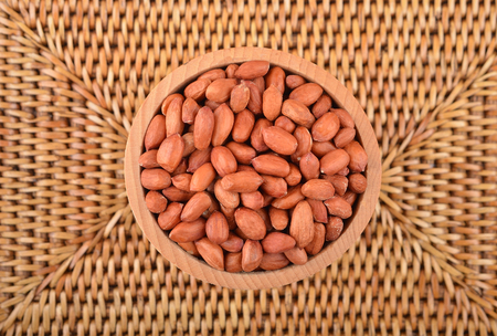 earthnut: Groundnuts in wooden bowl on wickered background