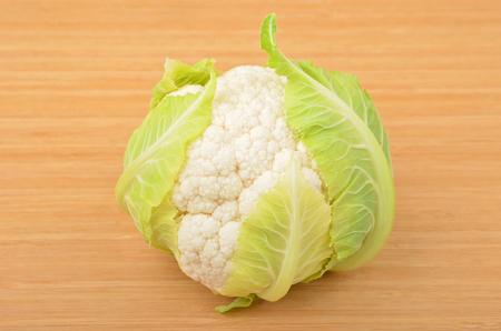 cruciferous: Whole ripe cauliflower, isolated on wooden background