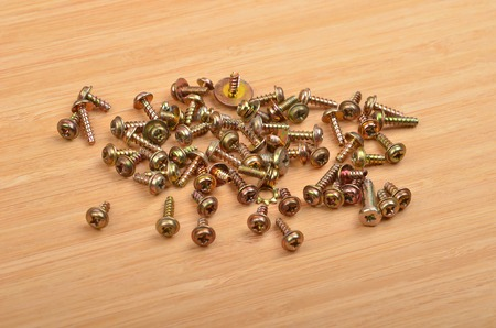 inflexible: Some screw on a natural wooden background Stock Photo