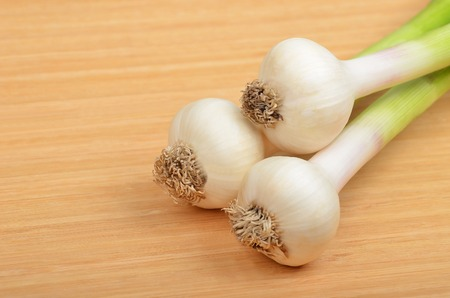 relish: Green garlic vegetable bulb on woooden background Stock Photo