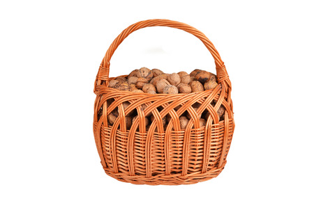 Walnut in a wattled basket, isolated on a white background Stock Photo