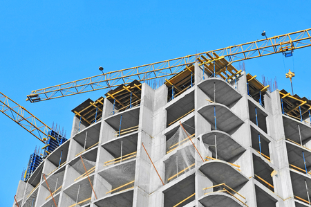 realestate: Building crane and building under construction against blue sky