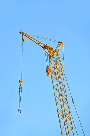 Mobile yellow construction tower crane against blue sky