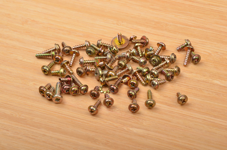Some screw on a natural wooden background Stock Photo