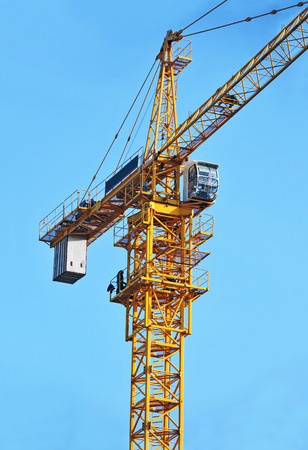 Yellow construction tower crane against blue sky Stock Photo