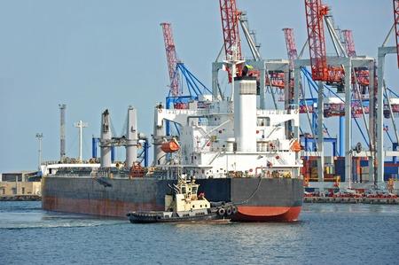 Tugboat assisting bulk cargo ship to harbor quayside Stock Photo