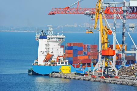 Container stack and ship under crane bridge Stock Photo